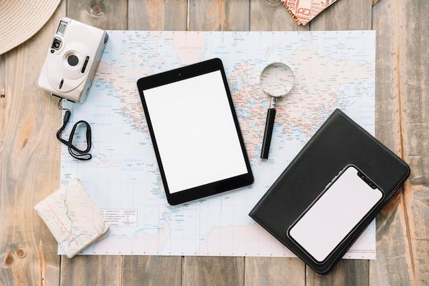 Bovenaanzicht van digitale tablet; mobiele telefoon; vergrootglas en dagboek op kaart tegen houten achtergrond