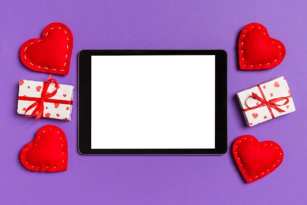 Bovenaanzicht van digitale tablet omringd met geschenkdozen en harten