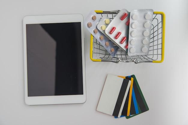 Bovenaanzicht van digitale tablet, winkelwagentje met pillen en creditcards. flatlay online shopping conceptie