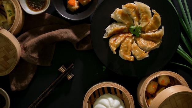 Bovenaanzicht van dim sum, gyoza, gezouten ei-varkensballetjes en broodje geserveerd op traditionele stoomboot