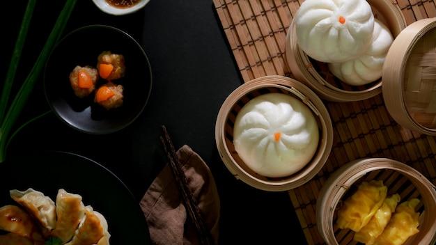 Bovenaanzicht van dim sum met broodjes, knoedels en gezouten eieren varkensvlees ballen in chinees restaurant