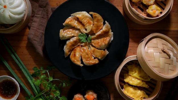 Bovenaanzicht van dim sum met gyoza, knoedels en broodje geserveerd op traditionele stoomboot