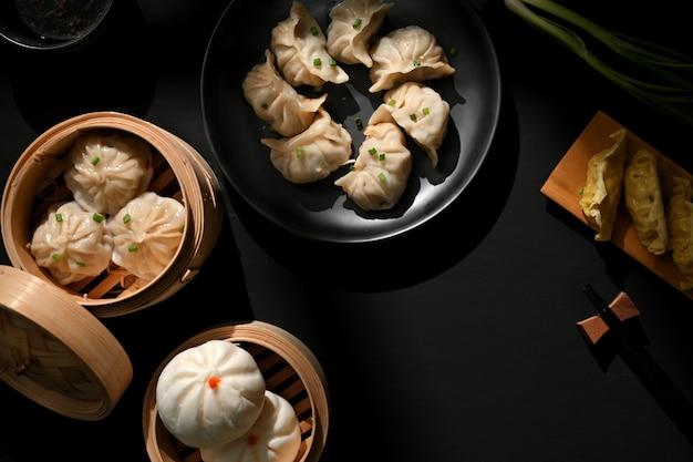 Bovenaanzicht van dimsum op plaat en bamboestoomboot met dumplings en varkensvleesbroodjes in chinees restaurant