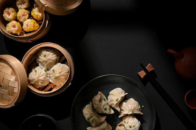 Bovenaanzicht van dimsum op plaat en bamboestoomboot met knoedels op tafel met kopie ruimte in chinees restaurant