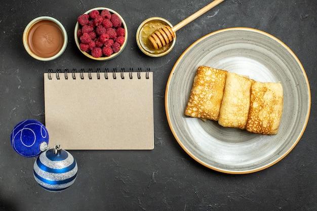 Bovenaanzicht van diner achtergrond met heerlijke pannenkoeken honing en chocolade framboos naast notebook decoratie accessoires op zwarte achtergrond