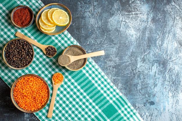 Bovenaanzicht van diner achtergrond met verschillende kruiden gele erwt op groene gestripte handdoek aan de rechterkant op donkere tafel