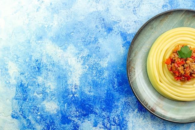 Bovenaanzicht van diner met heerlijke spagetti op een grijze plaat aan de linkerkant op blauwe achtergrond