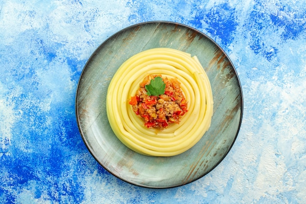 Bovenaanzicht van diner met heerlijke spagetti op een grijze plaat op blauwe achtergrond