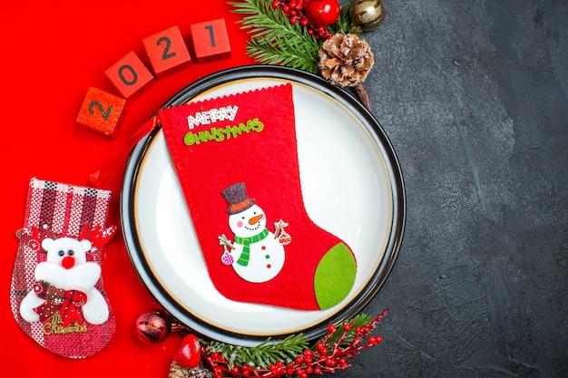 Bovenaanzicht van diner plaat decoratie accessoires fir takken en nummers kerst sok op een rood servet op een zwarte achtergrond