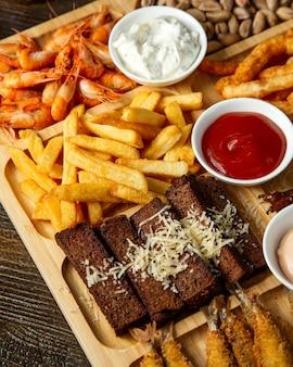 Bovenaanzicht van diverse biersnacks als gebakken broodstokken met kaasfrietjes, pistachenoten en gekookte garnalen met sauzen op een houten bord