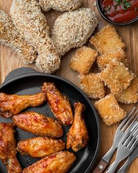 Bovenaanzicht van diverse gebakken kip met saus
