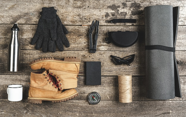 Bovenaanzicht van diverse hulpmiddelen voor wandeluitrusting op grunge hout