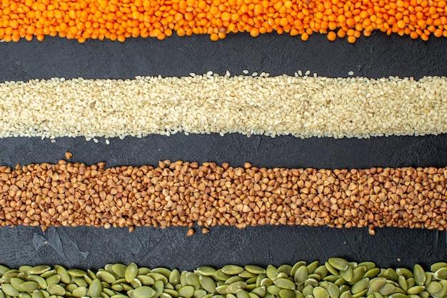 Bovenaanzicht van diverse korrels van boekweit pompoenpitten likdoorns rijst op zwarte achtergrond