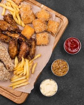 Bovenaanzicht van diverse sauzen met frietjes en gebakken kip
