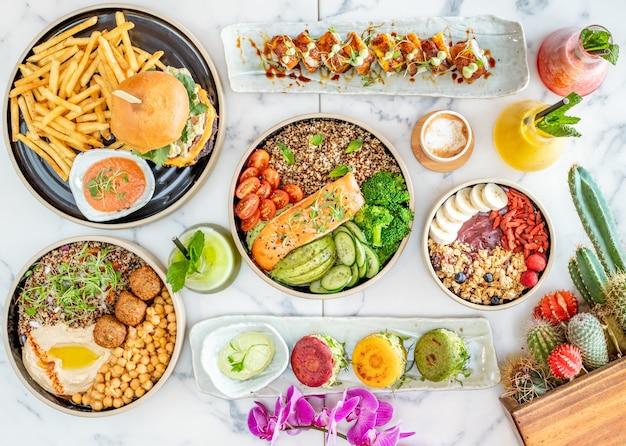 Bovenaanzicht van diverse smakelijke gerechten naast planten
