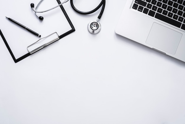 Bovenaanzicht van dokterspraktijk met stethoscooplaptop en klembord met kopieerruimte voor uw tekst