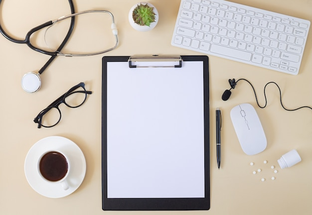 Bovenaanzicht van dokterstafel met stethoscoop, klembord, toetsenbord, microfoon, kopje koffie, pillen, glazen etc. online medisch consult concept