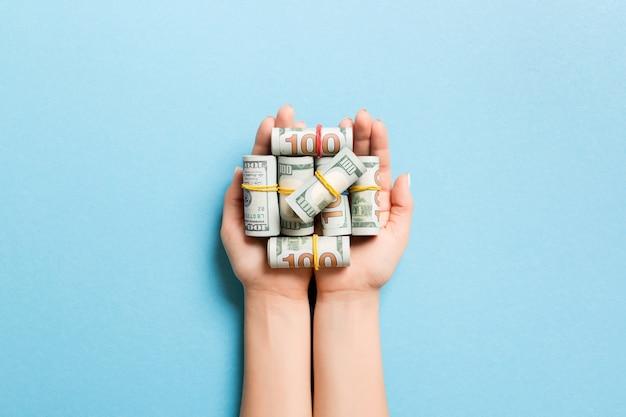 Bovenaanzicht van dollarbiljetten in buizen in vrouwelijke handen. bedrijfsconcept