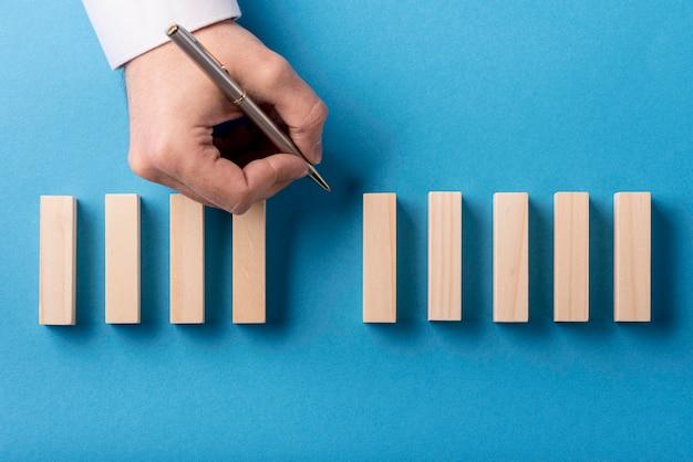 Bovenaanzicht van dominostukken en hand met pen