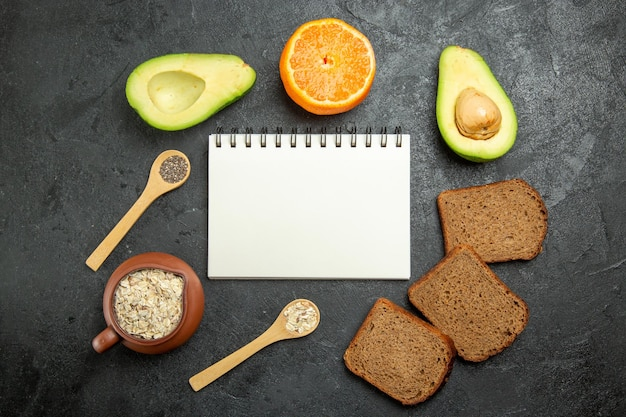 Bovenaanzicht van donker brood met avocado op grijze ondergrond