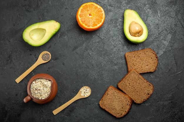 Bovenaanzicht van donker brood met avocado's op grijze ondergrond