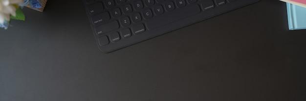 Bovenaanzicht van donkere concept werkruimte met draadloos toetsenbord en kopie ruimte