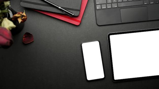 Bovenaanzicht van donkere creatieve plat lag werkruimte met digitale tablet briefpapier van smartphone en kopieer ruimte