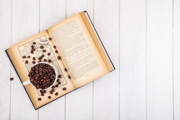 Bovenaanzicht van donkere gebrande koffiebonen op een witte kop op een witte houten achtergrond met kopie ruimte