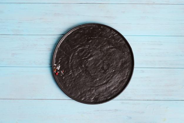Bovenaanzicht van donkere keramische plaat met kruiden en zout