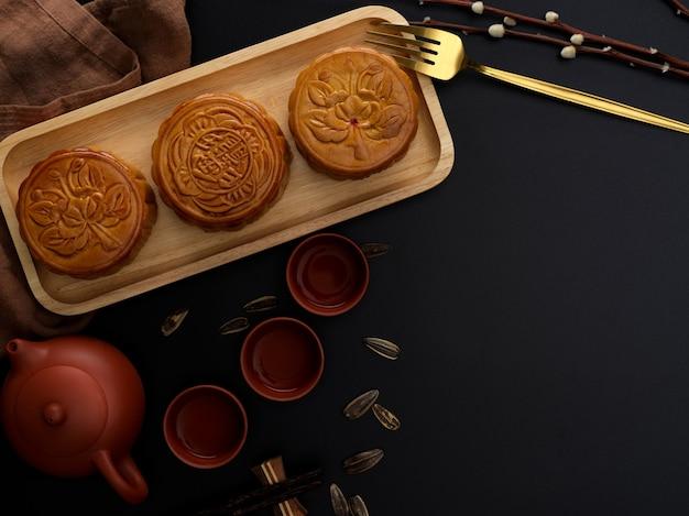 Bovenaanzicht van donkere moderne tafel met theeservies, maancakes op houten dienblad, decoratie en kopie ruimte. chinees karakter op de maancake vertegenwoordigt