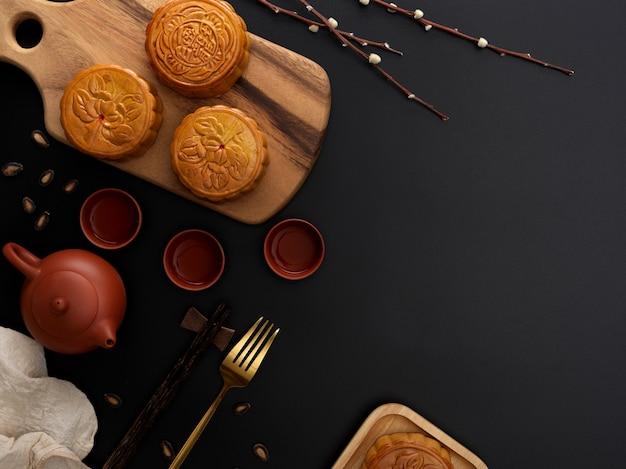 Bovenaanzicht van donkere moderne tafel met theeservies, maancakes op houten dienblad, vork, decoratie en kopie ruimte. chinees karakter op de maancake vertegenwoordigt