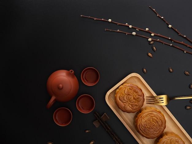 Bovenaanzicht van donkere moderne tafel met theeservies, maancakes op houten plaat, vork en kopie ruimte. chinees karakter op de maancake vertegenwoordigt
