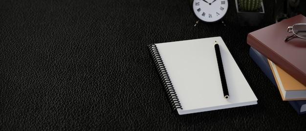 Bovenaanzicht van donkere moderne werkruimte met lege notebook en kantoorbenodigdheden