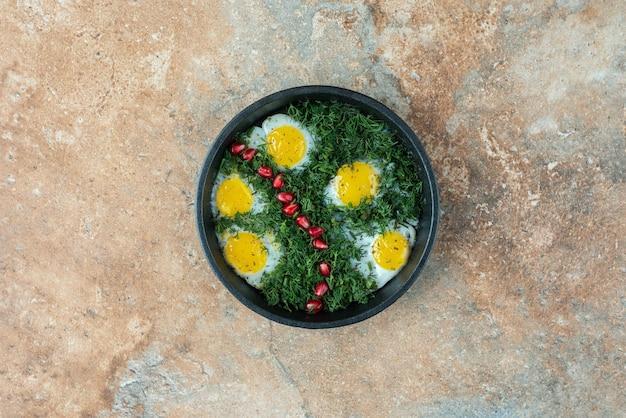 Bovenaanzicht van donkere pan met omelet en groenen.