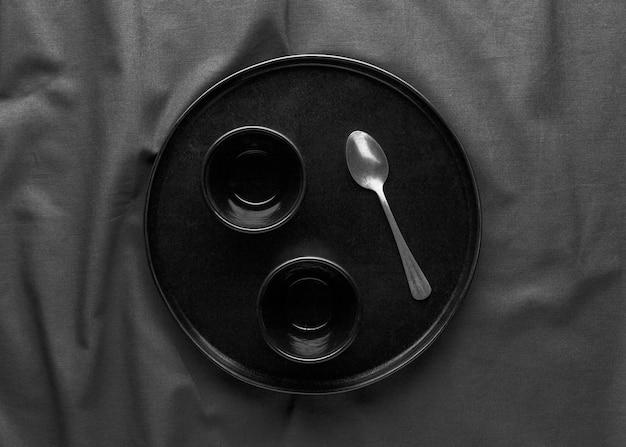Bovenaanzicht van donkere plaat met lepel