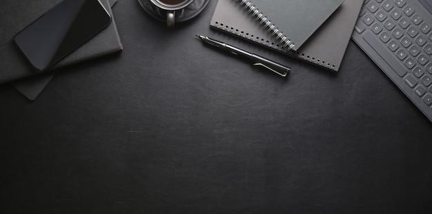 Bovenaanzicht van donkere stijlvolle werkplek met smartphone en kantoorbenodigdheden