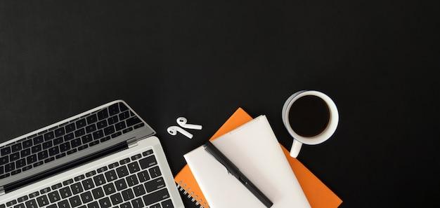 Bovenaanzicht van donkere trendy werkplek met laptop en kantoorbenodigdheden op zwarte tafel