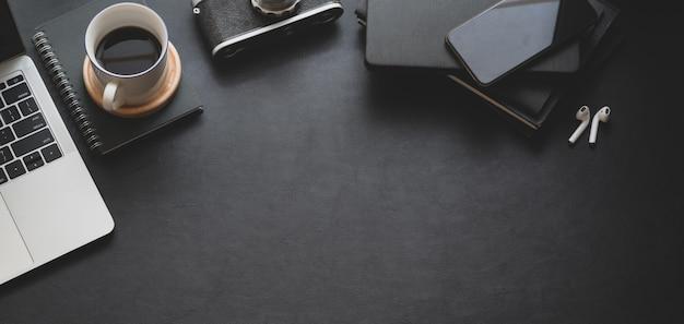 Bovenaanzicht van donkere trendy werkruimte met laptop, koffiekopje en kantoorbenodigdheden