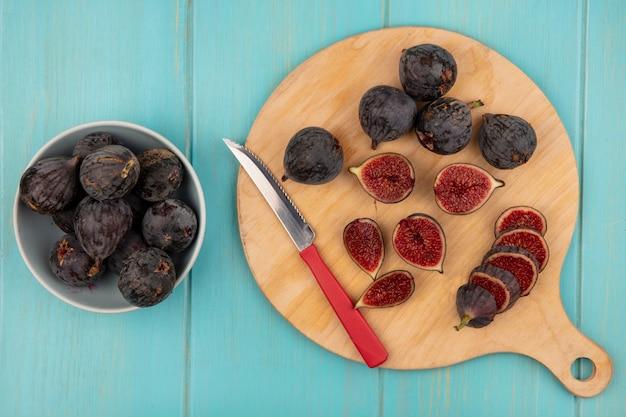 Bovenaanzicht van donkerpaarse missie vijgen op een houten keukenbord zwarte vijgen op een kom met mes op een blauwe houten muur