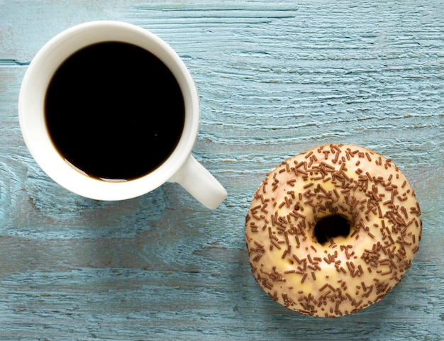 Bovenaanzicht van donut met hagelslag en koffie