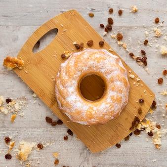 Bovenaanzicht van donut op snijplank met rozijnen