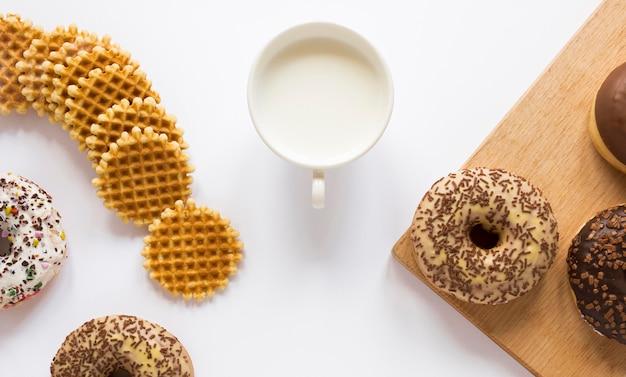 Bovenaanzicht van donuts en wafels met melk