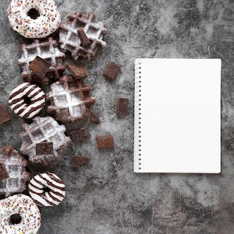 Bovenaanzicht van donuts met wafels en notebook