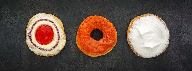 Bovenaanzicht van donuts op donkergrijze, grijze, zwarte toontextuur
