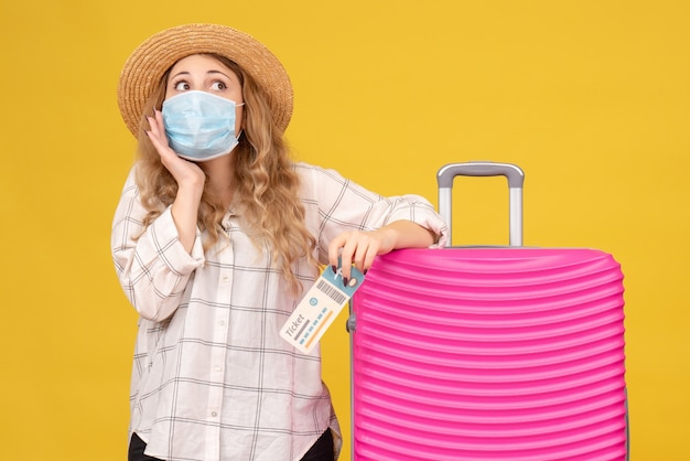 Bovenaanzicht van doordachte jonge dame masker tonen kaartje dragen en permanent in de buurt van haar roze tas
