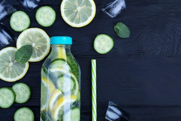 Bovenaanzicht van doordrenkt water met citroen, komkommer en munt in de fles
