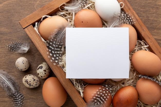 Bovenaanzicht van doos met eieren voor pasen en een stuk papier bovenop