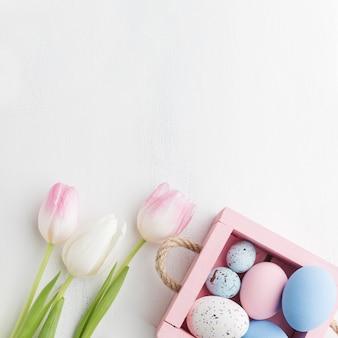 Bovenaanzicht van doos met kleurrijke paaseieren en tulpen