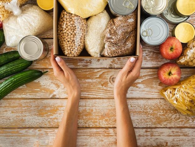 Bovenaanzicht van doos met voedsel voor donatie en handen