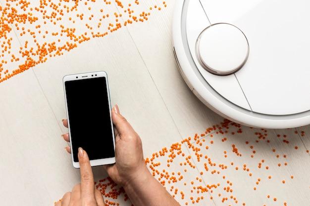 Bovenaanzicht van draadloos gestuurde stofzuiger met smartphone